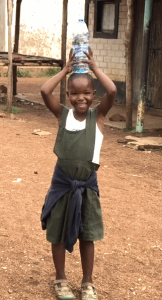 Though she's goofing off in this picture, it's common in Magzi's village to for kids to carry large buckets of water on their heads.